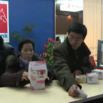 Customers with cell phones at Koryolink's service counter