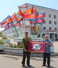 Members of the Intrepid DX group hold their banner next to a monument in the DPRK.