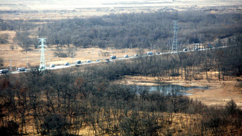 A convoy carrying manufactured goods from the Kaesong Industrial Park drives towards South Korea on March 22, 2010. (Donna Miles/DOD)