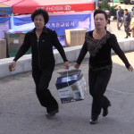Women carry a Panasonic rice cooker at the Pyongyang Spring International Trade Fair 2014 (P