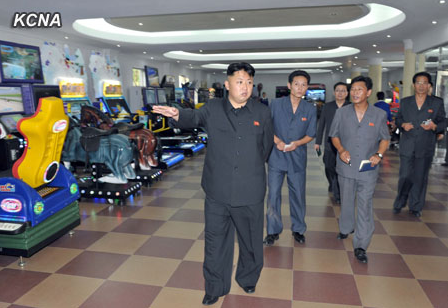 Kim Jong Un walks past video games in this KCNA photo