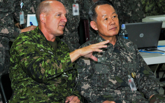 Admiral Choi Yoon Hee, Chairman of Joint Chiefs of Staff for the Republic of Korea, is briefed by Maj. Gen. Dean Milner, 1st Canadian Division Commanding General, about the operations at the 1st Canadian Division joint operation center in preparation for Ulchi Freedom Guardian exercise at Camp Yongin, South Korea, Aug. 20. (DOD Photo / Daniel Schroeder)