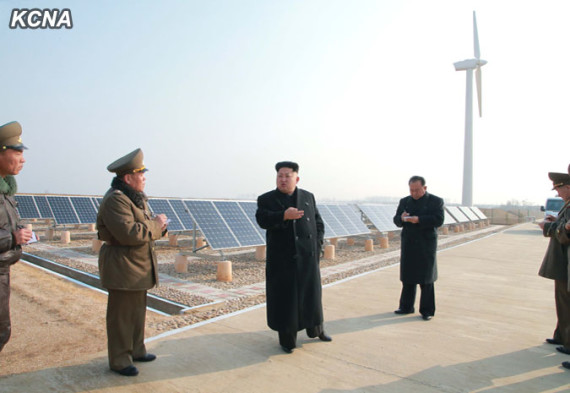 Kim Jong Un in front of solar panels in an image carried on the state KCNA newswire