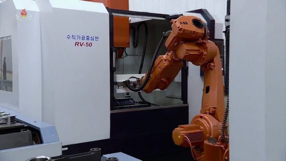 Image shows an orange industrial robot arm holding a piece of metal to a larger, white North Korean industrial machine in a factory