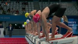 Image is a screenshot of TV coverage showing a swimming event about to start.