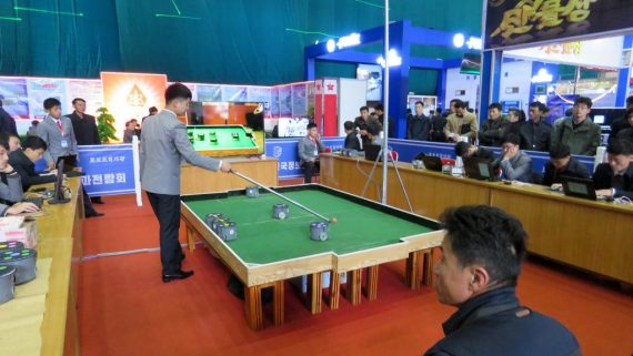 Image shows small robots on a table-sized football pitch. A person is standing nearby observing the robots.