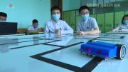 Two students look on while a small, two-wheeled robot follows a course marked out on a table top